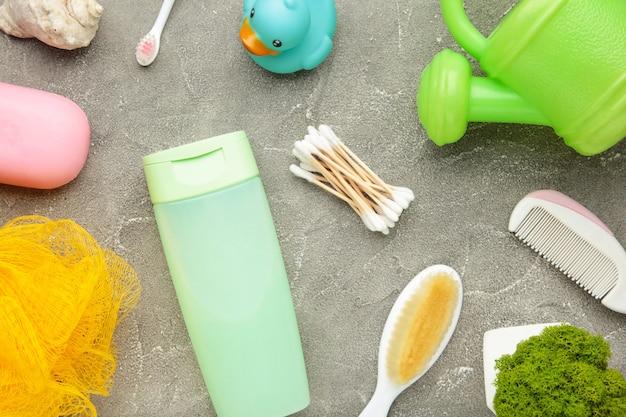Coisas de bebê de foto plana leigos. esponja, sabonete, gel de banho, pato de borracha, pente cinza. vista superior de cosméticos para bebês