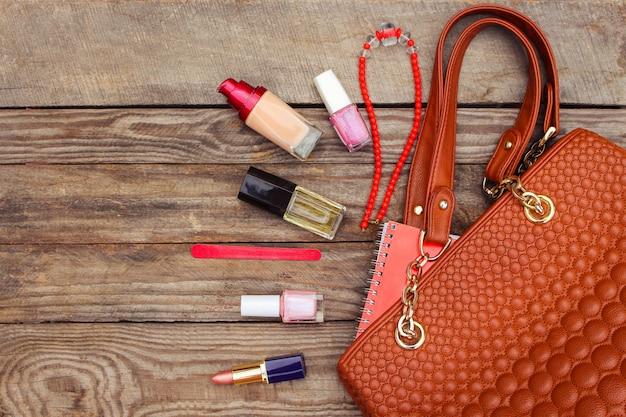 Coisas de bolsa de senhora aberta. bolsa das mulheres no fundo de madeira. imagem enfraquecida.
