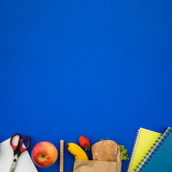 Coisas de escola e sanduíche no fundo azul
