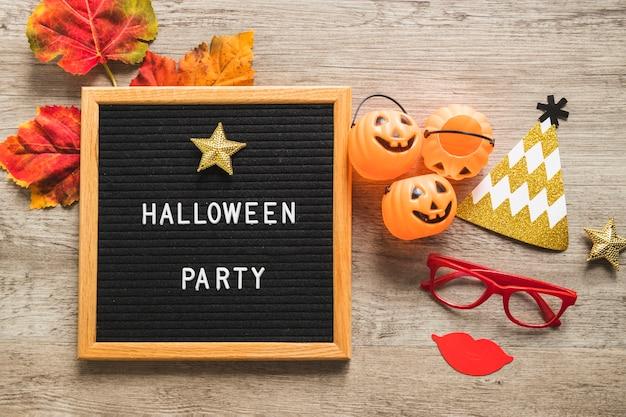 Coisas de halloween e folhas perto de quadro com a escrita
