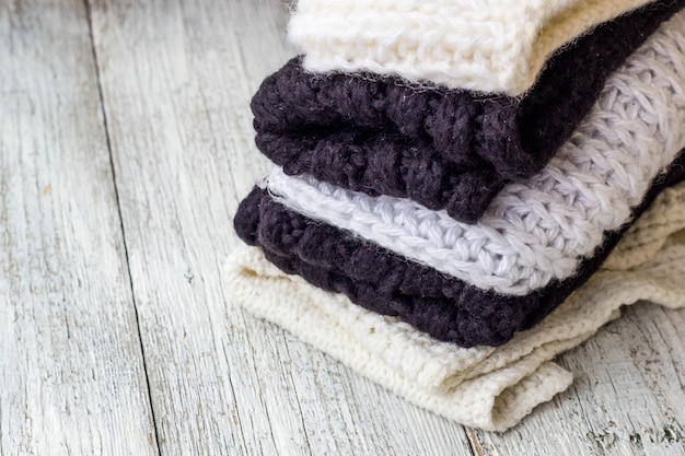 Coisas de malha dobradas brancas e pretas em um branco de madeira