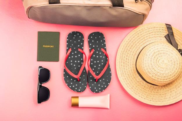 Coisas de mulher como bolsa de bagagem, chapéu, chinelos, loção, óculos escuros e passaporte para viajar