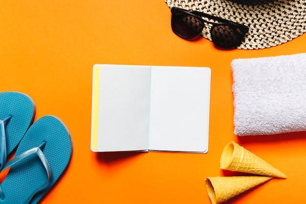 Coisas de resort de verão e notebook em fundo colorido