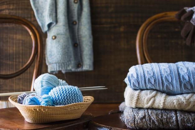 Coisas de tricô na cadeira perto de roupas