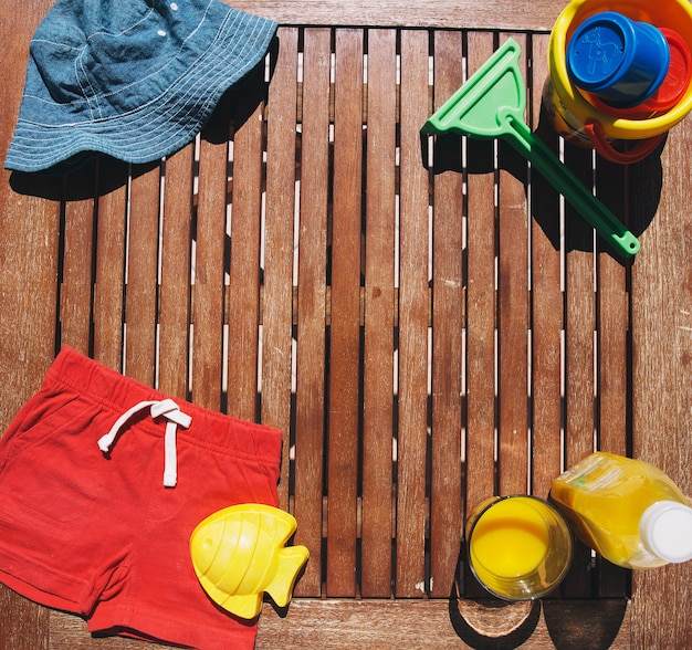 Coisas de verão bebê criança para a praia em um fundo de madeira. vista superior com espaço de cópia para o texto.