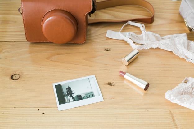 Coisas femininas compostas com câmera fotográfica