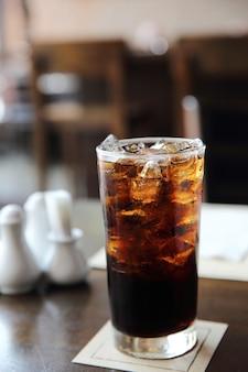 Cola bebendo em fundo de madeira