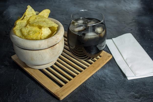 Cola com gelo e batata frita em tigela de madeira