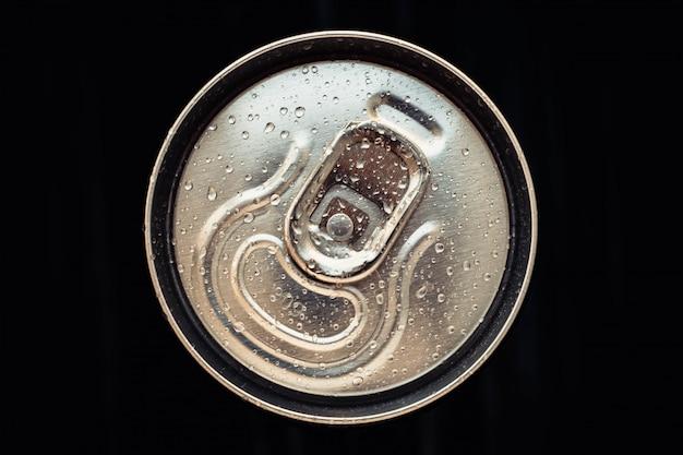 Cola de metal brilhante pode tampa com água cai sobre fundo preto. garrafa dourada de bebida, tampa da embalagem de cerveja. vista do topo.