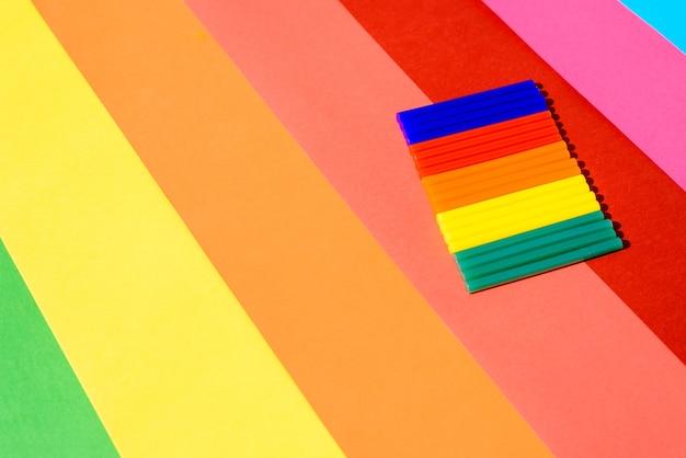 Cola de silicone colorida em um fundo de linhas vibrantes.