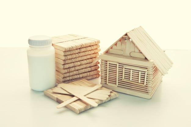 Cola e pilha de vara de madeira de picolé fazendo crianças em casa