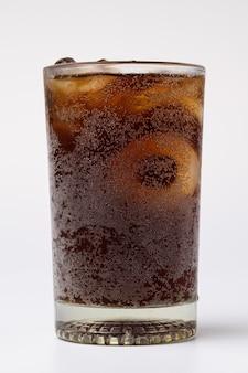 Cola em copo com cubos de gelo transparente no fundo branco