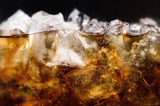Cola em copo com cubos de gelo transparentes