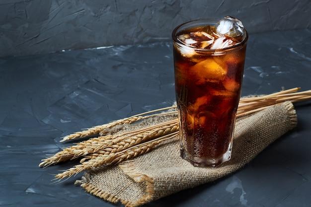 Cola escura fria com cubos de gelo