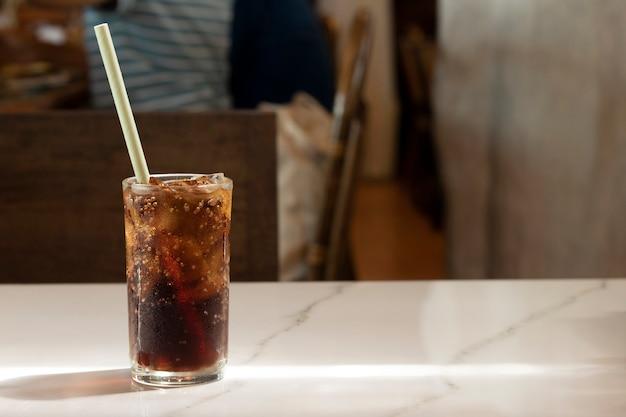 Cola fria refrigerante cubo de gelo em um refresco com sede de vidro na mesa no restaurante