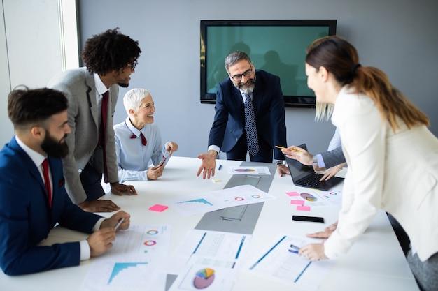 Colaboração e análise por empresários que trabalham em escritórios modernos