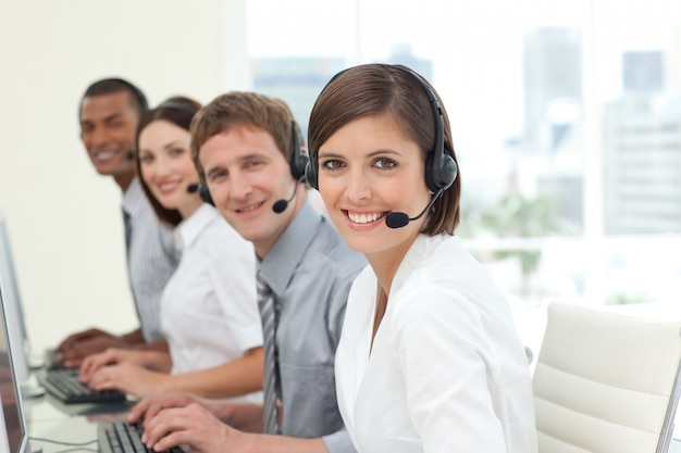 Colaboradores felizes com fones de ouvido no trabalho no call center