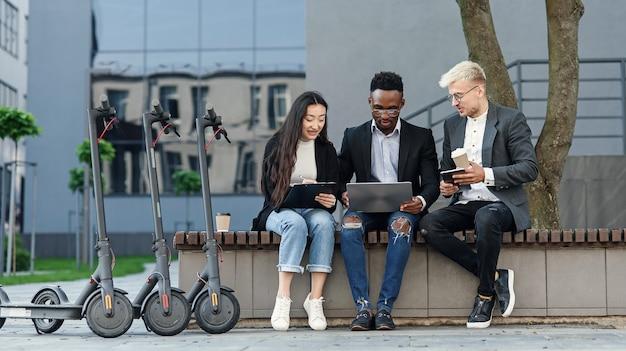 Colaboradores internacionais confiantes sentados em um banco de madeira em frente ao escritório e discutindo os resultados