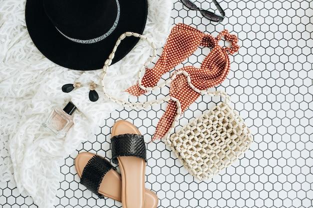 Colagem de moda plana leiga com acessórios modernos femininos em azulejo de mosaico branco. chinelos, chapéu, bolsa de mão, perfume, brincos, óculos de sol