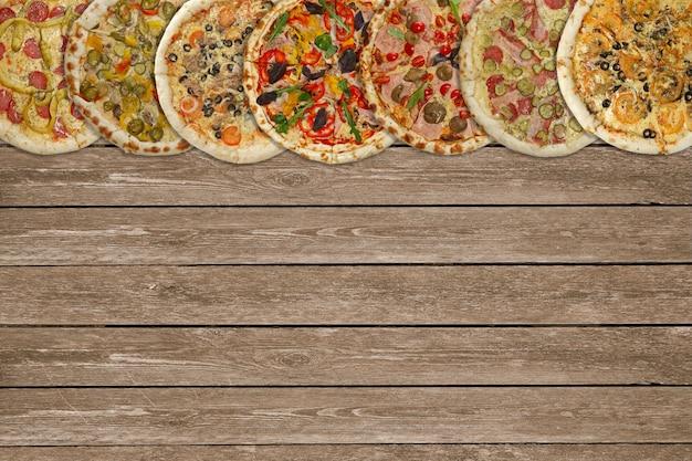 Colagem horizontal de diferentes pizzas assadas na mesa de madeira escura. vista do topo.