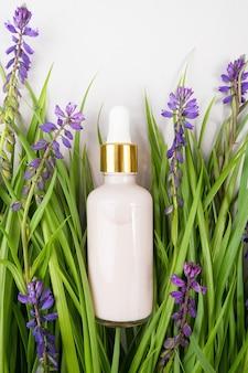 Colágeno anti-envelhecimento rosa, soro facial ou outro produto cosmético em frasco de vidro entre a grama verde, flores roxas em fundo cinza. maquete do conceito cosmético natural organic spa.