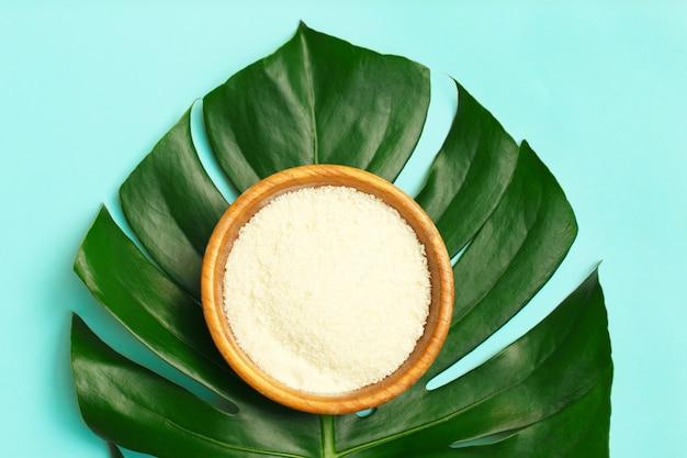 Colágeno em pó na tigela em folha de palmeira.