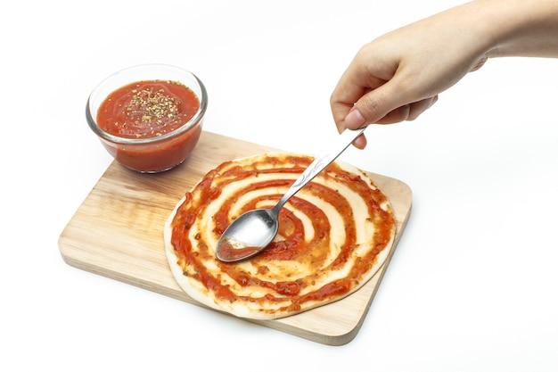 Colando o molho de pizza na massa de pizza