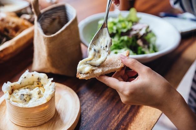 Colando o queijo do brie no pão pelas mãos com salada verde do carvalho no fundo.