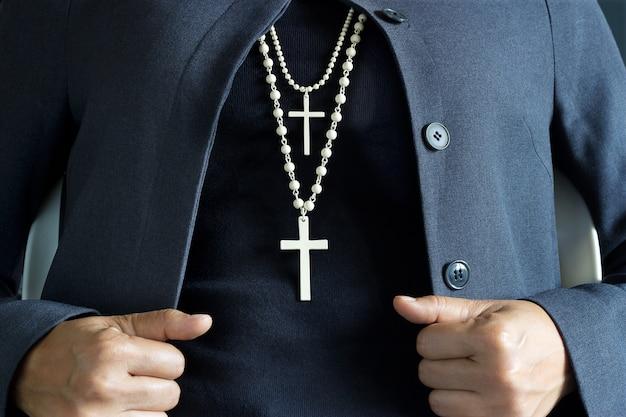 Colar crucifixo branco no pescoço