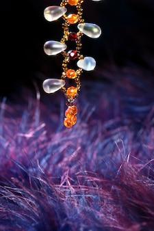 Colar de joia laranja sobre pena roxa azul