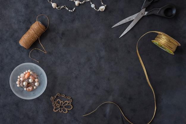 Colar de miçangas; fio marrom; tesoura; fita dourada; contas e pulseira de metal no pano de fundo texturizado preto