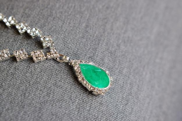 Colar de ouro branco cravejado de esmeralda, rodeado de diamantes
