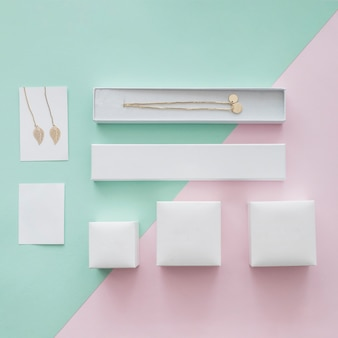 Colar de ouro e brincos com caixas diferentes em fundo pastel