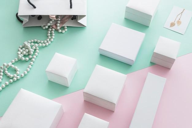 Colar de pérolas brancas com diferentes caixas brancas em fundo de papel pastel