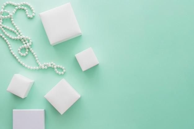 Colar de pérolas brancas com variedade de caixas brancas sobre fundo de papel verde pálido