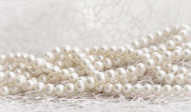 Colar de pérolas brancas da natureza em foco suave com destaques