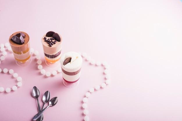 Colar de pérolas brancas e colheres perto do pudim de chocolate e baunilha em copos