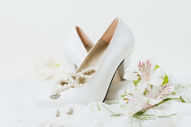 Colar de pérolas; brincos; salto alto de casamento e buquê de flores no cachecol