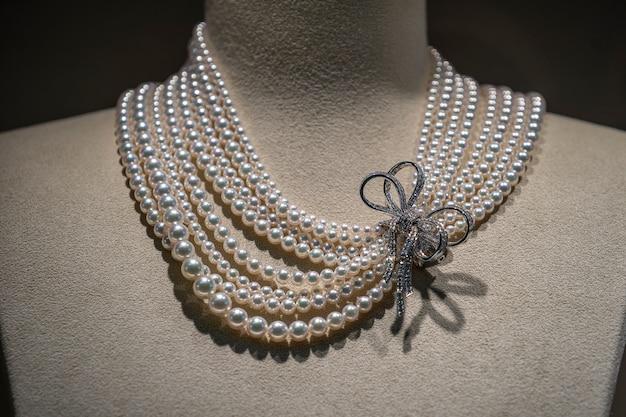 Colar de pérolas de luxo com pedras preciosas em moldura dourada branca em manequim, close-up