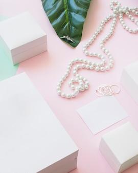 Colar de pérolas e brincos com caixas brancas em fundo rosa