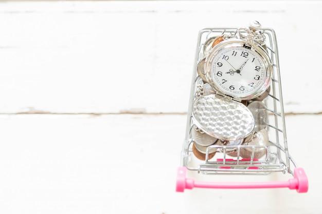 Colar e moeda de prata bonitas do relógio no mini carrinho de compras.