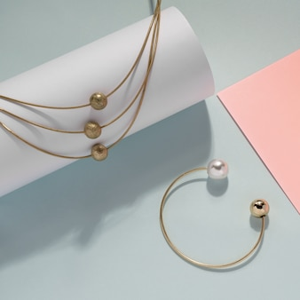 Colar e pulseira de ouro com pérolas no fundo da cor pastel