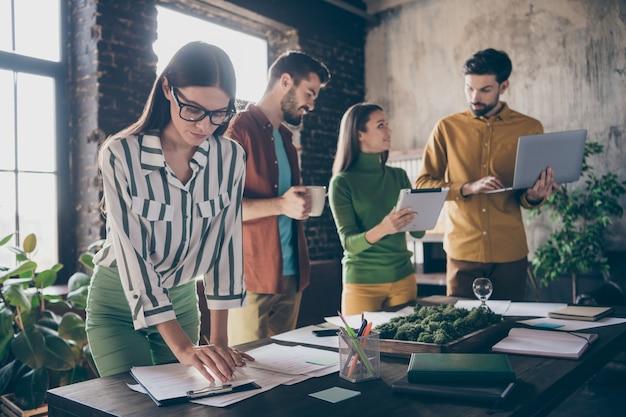 Colares de ceo experientes concentrados positivos do grupo apreciam o trabalho estratégia de desenvolvimento de start-up segurar computador