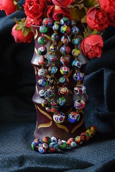 Colares de miçangas millefiori no vaso com rosas em fundo de seda tailandesa
