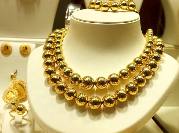 Colares de ouro, miçangas e anéis