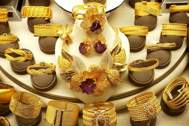 Colares e anéis de ouro e pulseiras em suportes