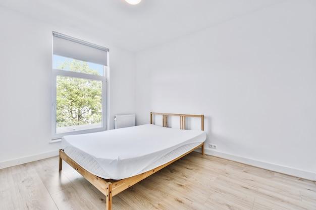 Colchão macio com lençol branco colocado na cama de madeira perto da janela em um quarto claro em casa