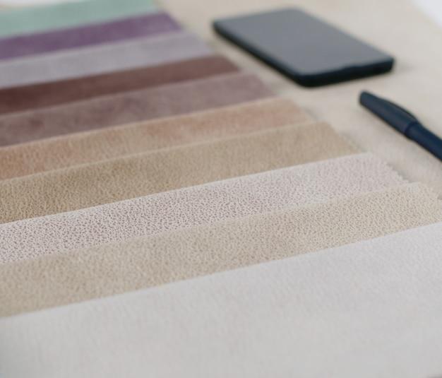 Coleção brilhante de amostras coloridas de têxteis com textura de camurça. amostras de tecido, smartphone e carteira.