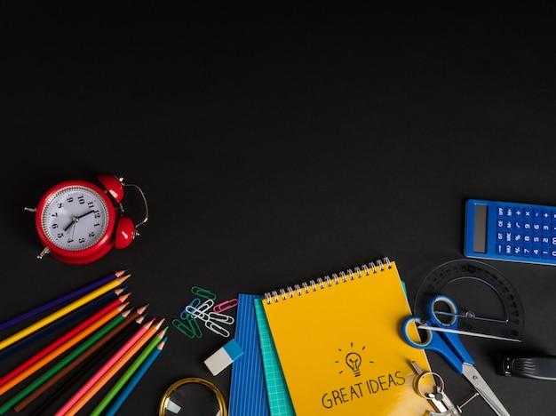 Coleção colorida de material escolar em fundo preto. de volta à escola. vista do topo