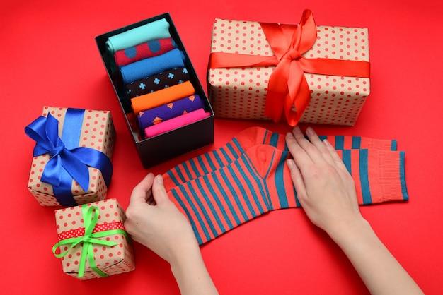 Coleção colorida de meias de algodão como um presente nas mãos da mulher.